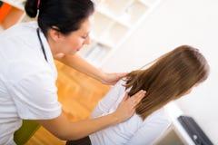 Chiropractor que hace el ajuste en paciente femenino Foto de archivo libre de regalías