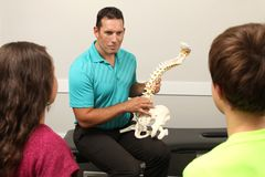 Chiropractor. A Chiropractor showing a model of the human spine to two children Stock Photography