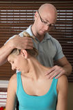 Chiropractor stretchesfemale patient neck muscles Stock Photo