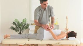 Chiropractor stretching the back of a woman stock video