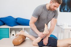 Chiropractor stretching boy's leg. Image of male chiropractor stretching boy's leg royalty free stock photography
