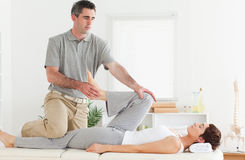 Chiropractor stretching customer's leg