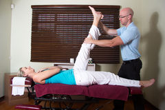 Chiropractor stretching female patient leg upright Stock Photos