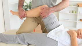 Chiropractor stretching the knee of a woman stock footage
