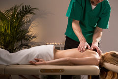 Chiropractor treating young woman Stock Images