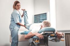 Chiropraktor in der blauen Uniform Beine des älteren Mannes überprüfend stockbild