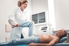 Chiropraktor, der ihren Patienten liegt auf Bett überprüft stockbild