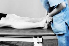 Chiropraktor /physiotherapist, das eine Fußmassage im silhouet tut stockfotos