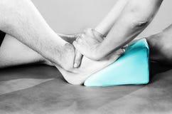 Chiropraktor /physiotherapist, das eine Fußmassage im silhouett tut stockbild