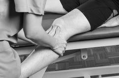 Chiropraktor /physiotherapist, das eine Kniemassage tut stockbild