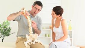 Chiropratico che spiega la spina dorsale ad una donna video d archivio