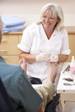 Chirpodist treating client in clinic Royalty Free Stock Photos