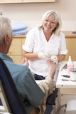 Chirpodist treating client in clinic Stock Photo