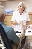 Chirpodist treating client in clinic Stock Photos