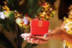 Chirstmas礼物盒在手边有Xmas树的 库存图片