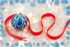 Chirstmas bauble with red ribbon. On bokeh background with snowflakes Royalty Free Stock Photo