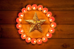 Chirstmas candles circle over wood and symbol. Chirstmas candles circle over wood and golden star symbol Stock Photography