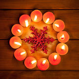 Chirstmas candles circle over wood and symbol. Chirstmas candles circle over wood and red snowflake symbol Royalty Free Stock Images