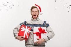 Chirstmas Concept - Happy young caucasian beard man holding present box with confetti background celebrating for. Christmas day Royalty Free Stock Photography
