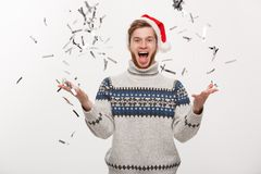 Chirstmas Concept - Happy young caucasian beard man throwing confetti celebrating for Christmas day. Chirstmas Concept - Happy young caucasian beard man Royalty Free Stock Image