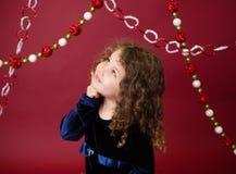 Chirstmas-Kind mit Verzierungen und Dekorationen, roter Feiertags-Winter Stockfotografie