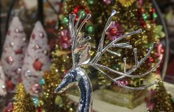 Chirstmas Wonderland - shiny silver deer head with long graceful antlers in front of blurred bokeh colorful trees in holiday setti royalty free stock image