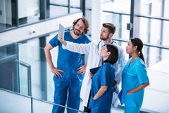 Chirurdzy, lekarka i pielęgniarka patrzeje cyfrową pastylkę, obrazy stock