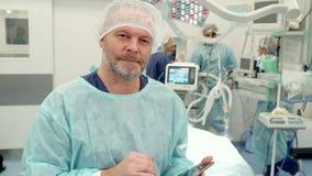 Chirurg benutzt Tablette am Chirurgieraum stockfotografie