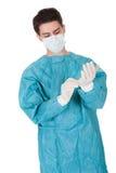 Chirurg, der auf chirurgische Handschuhe sich setzt Stockfotografie