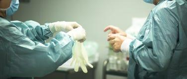 Chirurg, der auf Handschuhe sich setzt Stockbild