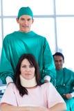 Chirurg, der einen Patienten auf einem Rollstuhl trägt Lizenzfreie Stockfotos
