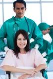 Chirurg, der einen weiblichen Patienten auf einem Rollstuhl trägt Stockfotografie