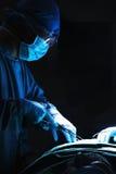 Chirurg, der unten schaut, bearbeitet und chirurgische Ausrüstung mit dem Patienten liegt auf dem Operationstisch hält Stockbild