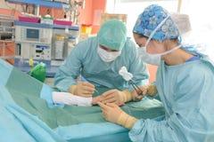Chirurg die handeling op patiëntenhand uitvoeren royalty-vrije stock afbeelding