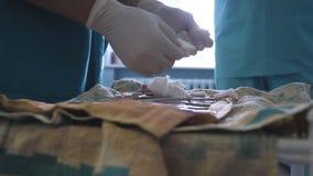 Chirurg die in handschoenen instrumenten voorbereiden vóór chirurgie De arts bereidt de hulpmiddelen voor chirurgie voor Sluit om stock footage