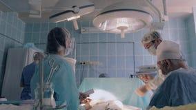Chirurg die het licht draaien onder correcte hoek om chirurgie voort te zetten stock video