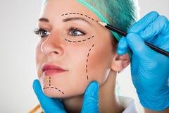 Chirurg Drawing Perforation Lines auf Frau ` s Gesicht stockbild