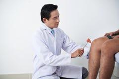 Chirurg egzamininuje kolanowego odruch zdjęcie royalty free