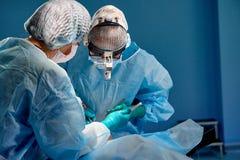 Chirurg en zijn hulp het presteren kosmetische chirurgie in het ziekenhuis werkende ruimte Chirurg in masker die loupes dragen ti royalty-vrije stock foto's