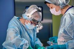 Chirurg en zijn hulp het presteren kosmetische chirurgie in het ziekenhuis werkende ruimte Chirurg in masker die loupes dragen ti stock foto's