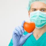 Chirurg in groen eenvormig holdingsstuk speelgoed hart ter beschikking - geneeskunde en gezondheidszorgsymbolen Royalty-vrije Stock Afbeelding