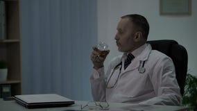 Chirurg het ontspannen na harde verrichting het drinken alcohol en het nadenken zijn acties stock footage