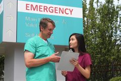 Chirurg, lekarka, lekarz, klinicysta i Azjatycka pielęgniarka Jest ubranym pętaczka stojaka przed Szpitalnym izba pogotowia znaki Obrazy Royalty Free