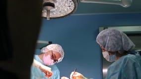 Chirurg op het werk een team van professionele chirurgen voert chirurgie op de patiënt uit Echte werkende ruimte MEDISCH concept stock video