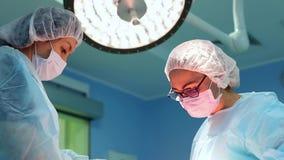 Chirurg op het werk een team van professionele chirurgen voert chirurgie op de patiënt uit Echte werkende ruimte MEDISCH concept stock videobeelden