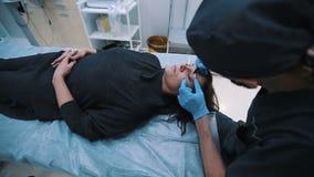 Chirurg plastyczny sprawdza w średnim wieku kobiety twarz przed chirurgią plastyczną zdjęcie wideo