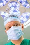 Chirurg in verrichtingsruimte met lamp op achtergrond. Royalty-vrije Stock Foto