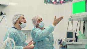 Chirurg zeigt seine Hand auf dem Monitor lizenzfreies stockfoto