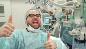 Chirurg zeigt sich seine Daumen lizenzfreie stockfotos