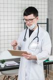 Chirurgdoktor mit Tablet-Computer im Krankenhausbüro Medizinischer Gesundheitswesenpersonal- und -doktorservice stockfotografie